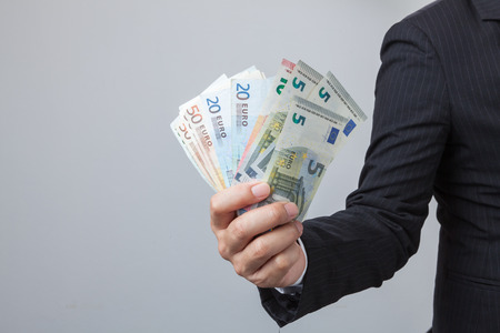 one hundred euro banknote: Business Man Displaying a Spread of Cash over isolated a white background