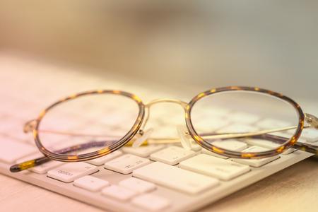 wayfarer: Keyboard and glasses on wooden dresk at office.