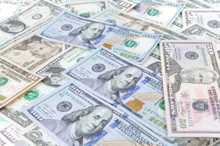 counterfeiting: Multiple scattered American 100 dollar banknotes in full frame coverage with corner vignetting viewed from above in a conceptual financial background