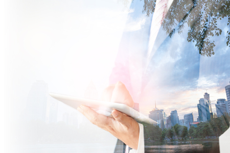 Double exposure of a businessman and a green city using a tablet over white background Stock Photo