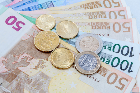 Money euro coins and banknotes in studio on white background.