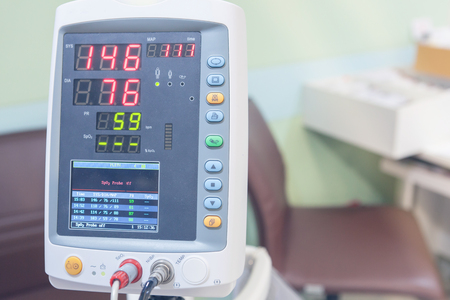 hospital trolley: A Hospital Vital Sign Monitor on Trolley with Blood Pressure Cuff and Thermometer on hospital background.
