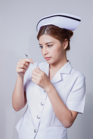 Young woman asian nurse attractive beauty brunette focus holding hypodermic syringe in white background