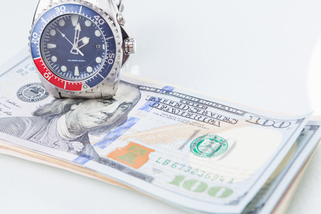 buying time: Buying time  Euro coin dollar banknote trying to buy a clock. Stock Photo