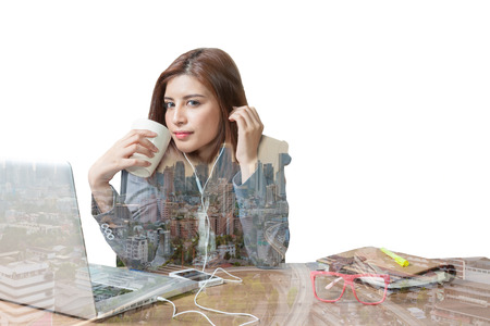 Double exposure Business woman attractive beautiful sitting at office desk and enjoy with listening music and drinking coffee relaxation smile and Bangkok city view background as a concept. photo
