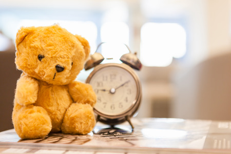 niños abandonados: Retro Teddy Bear toy alone with alam clock in lunch time on vintage wall background.