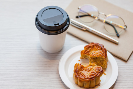 A Chiness moon cake with a hot disposable coffee cup on the wooden table at working room  2 Chiness capital letters are wish and not trade mark.