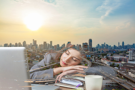 power nap: Double exposure business woman sleeping on laptop taking a power nap during work and Bangkok city view background as a concept