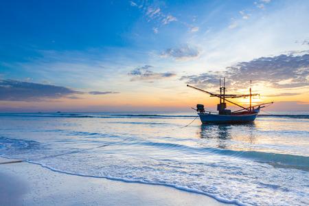 An impressive sunrise over the sea with boats at Hua Hin beach, Thailand.