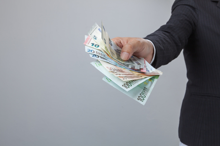 displaying: Business Man Displaying a Spread of Cash over isolated a white background