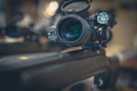 Closeup of a sniper rifle telescope glass lens on shop background Stock Photo