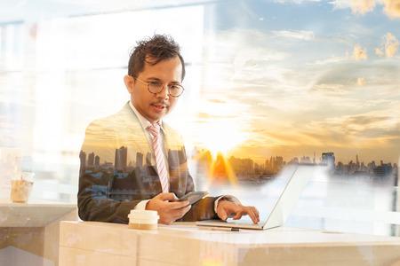 La doppia esposizione di un imprenditore di successo sta lavorando in una società d'ufficio con net-book e touch smart phone per l'analisi della finanza. Vista aerea del tramonto drammatico & del cielo blu a Bangkok Tailandia dell'asiatico. Archivio Fotografico - 94159323