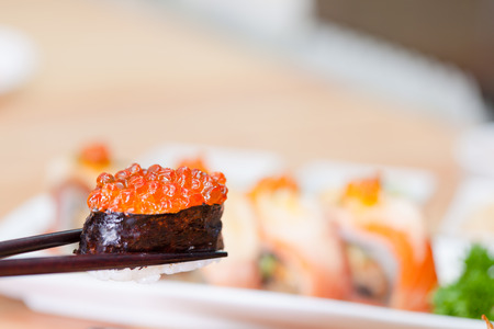 Sushi with chopsticks which show roll made of smoked fish and roe, japanese  food concept.
