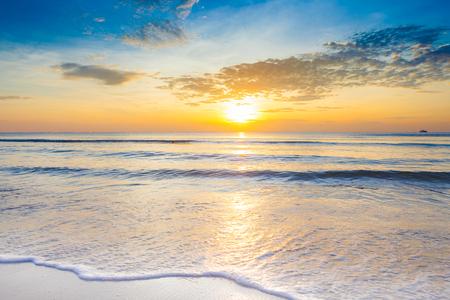 Salida del sol brillante sobre la playa un impresionante en la playa de Hua Hin, Tailandia.