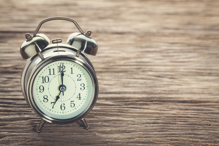 Clock at 7 Oclock in the morning with vintage style alarm clock on a wooden table. Stock Photo