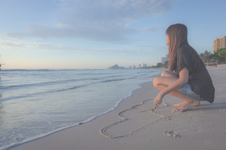 woman drawing a heart in the sand on a tropical beach Stock fotó