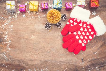 Guanto con decorazione natalizia su tavola di legno. Decorazione invernale Archivio Fotografico - 92523100
