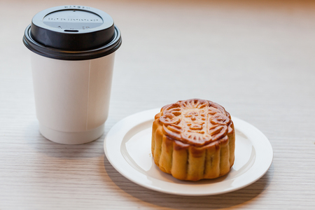 A Chiness moon cake with a hot disposable coffee cup on the wooden table  2 Chiness capital letters are wish and not trade mark.
