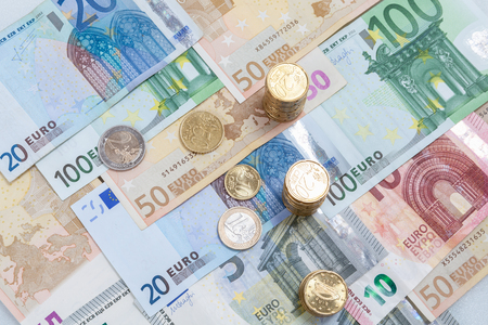 euro money stacks and banknotes on white background.