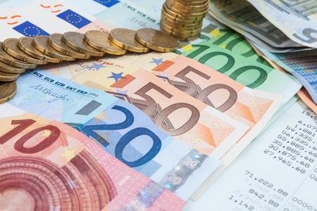 Conto di conto con i soldi in cima / esamina i vantaggi contabili in molte banconote in euro Archivio Fotografico - 92523034