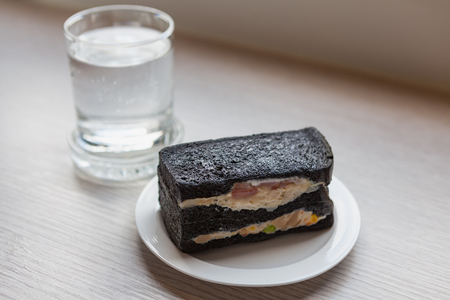 Charcoal sandwiches with Oclock and a glass of dringking water in morning time on wooden table in working room