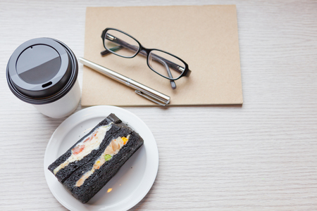 a disposable coffee cup with charcoal sandwiches and diary on wooden table in vintage romace