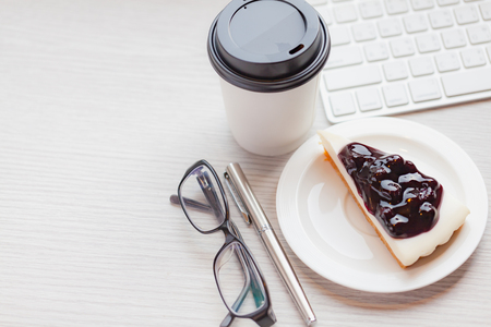 Disposable coffee cup with blueberry chess pie on wooden table in working room.