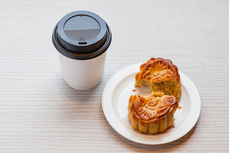A Chiness moon cake with a hot disposable coffee cup on the wooden table / 2 Chiness capital letters are wish and not trade mark. Stock Photo