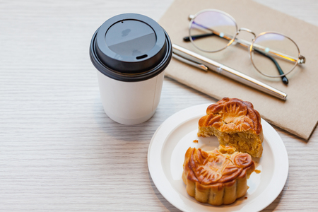 A Chiness moon cake with a hot disposable coffee cup on the wooden table at working room / 2 Chiness capital letters are wish and not trade mark.