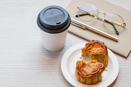 Una torta di luna Chiness con una tazza di caffè usa e getta calda sul tavolo di legno nella sala di lavoro / 2 lettere maiuscole Chiness sono desiderio e non marchio. Archivio Fotografico - 92523044