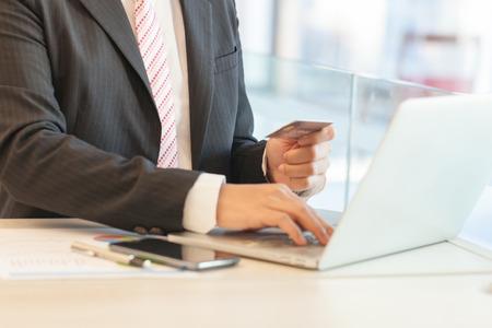 Uomo d'affari facendo operazioni bancarie online, effettuare un pagamento o acquistare beni su Internet inserendo i dettagli della sua carta di credito su un computer portatile, vista ravvicinata delle sue mani Archivio Fotografico - 92523113
