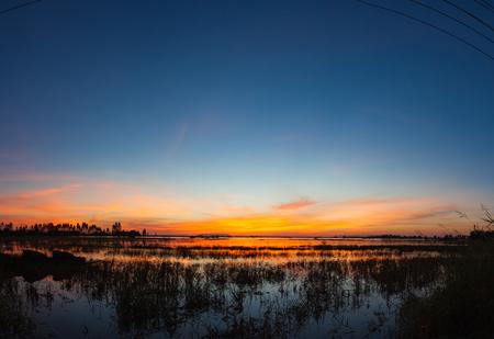 Panoramic sunset reflection in a lake at Ubonrat dam, Khon Khan city, Thailand.