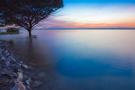 Tramonto con la riflessione dell'albero in un lago alla diga di Ubonrat, città di Khon Khan, Tailandia. Archivio Fotografico - 92523127