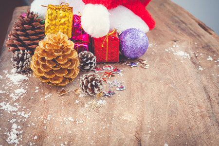 Christmas background with christmas ball, gift, red hat and snow on a wooden background/ Christmas background Stock Photo