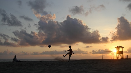 Football on the beach during sunset photo