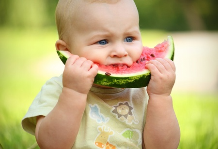 little baby eating watermelon outdoors Stock Photo