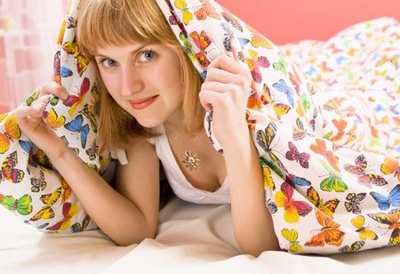 blonde girl lying under a blanket with butterflies