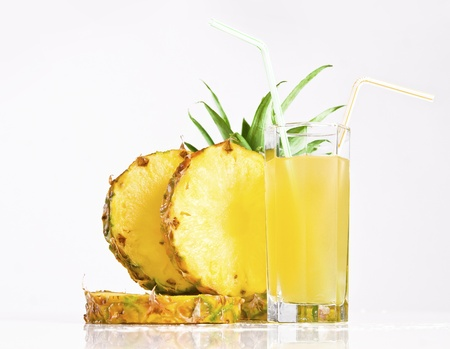 Fresh pineapple juice with sliced pineapple on white background