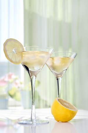 Martini alcohol cocktail with yellow lemon on white table photo
