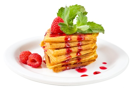 Plate of belgian waffles with fresh raspberries, mint and jam photo