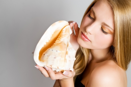 Glamour portrait of beautiful blond woman model with fresh daily makeup and healthy hair  Fashion shiny highlighter on skin and sexy gloss lips make-up  Girl with seashell photo