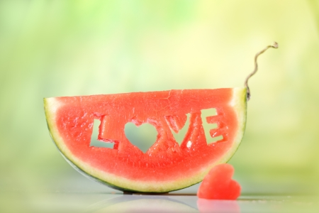 natural love: Fresh juicy watermelon slice on natural green background close-up with love letters word Stock Photo