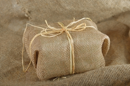 Burlap gift on the canvas texture