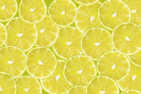 Abstract yellow background with citrus-fruit of lime slices. Close-up pattern.