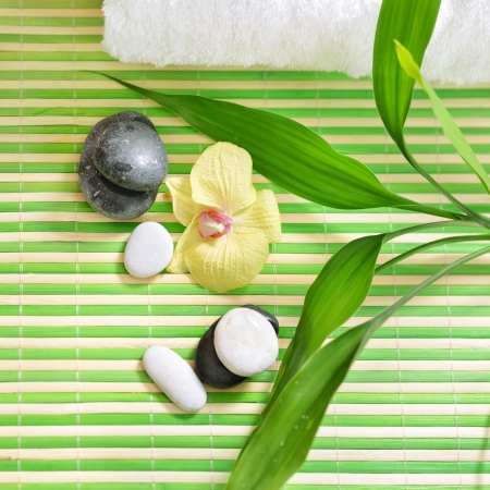 Spa treatment with stones, orchid flower and green bamboo. Top view. Stock Photo
