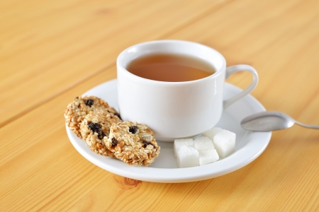 Tea cup with taste cakes and sugar photo