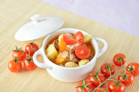 A bowl of healthy potato soup with carrot, tomatoes and meat
