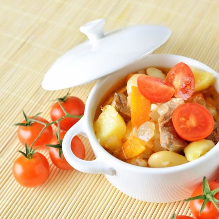 A bowl of healthy vegetable soup with potato, carrot, tomatoes and meat.
