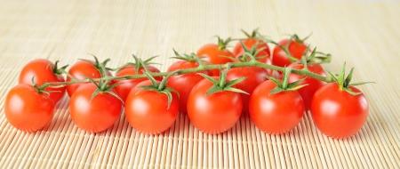 panorama of fresh cherry tomatoes on bamboo background