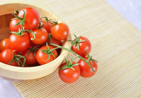 fresh cherry tomatoes on the vine in a wooden plate on bamboo background